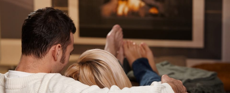 couple sitting in front of fire