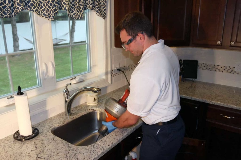Technician cleaning out sink